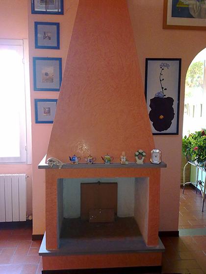 La parte bassa del soggiorno a doppio volume con il caminetto esistente